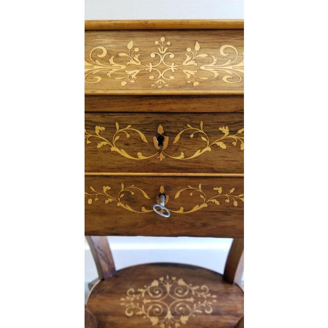 A fine antique rosewood vanity with satinwood marquetry. Mirrored and fitted interior. Retaining original castors, circa...