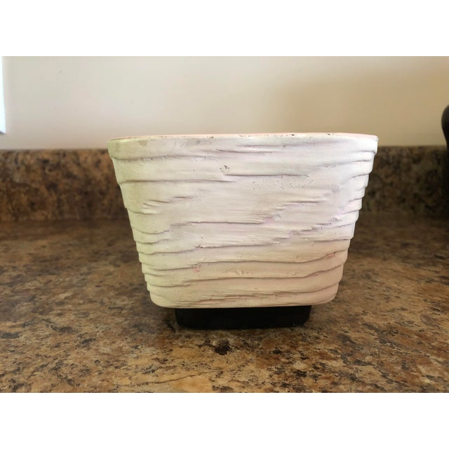 This pale pink rectangular planter has rounded corners and a wood grain textured finish. The inside is glazed a darker...