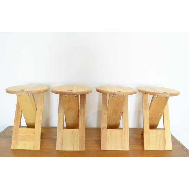 Pair of foldable stools with Round Top and X legs, finger hole on top. by Roger Tallon, 1970. materials: maple wood