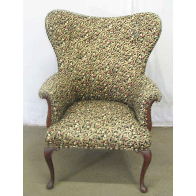 Antique wingback parlor chair Reupholstered chair with mahogany feet and arms.