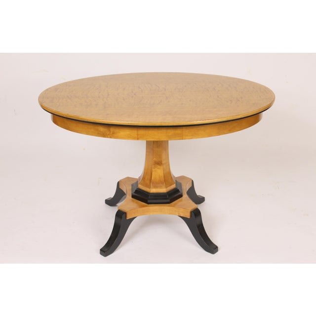 Biedermeier style oval occasional / center table with a feathered birch top and ebonized decoration on the base and feet,...