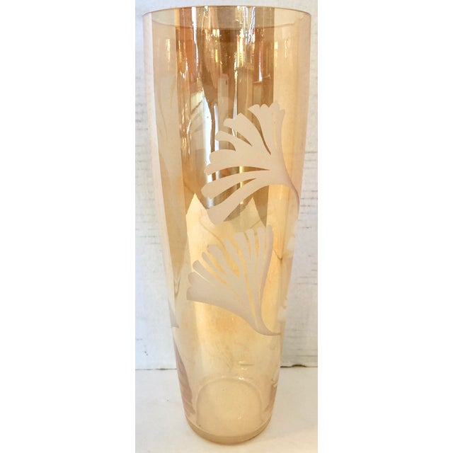 Tall vintage vase in gold glass with leaves etched on the exterior.