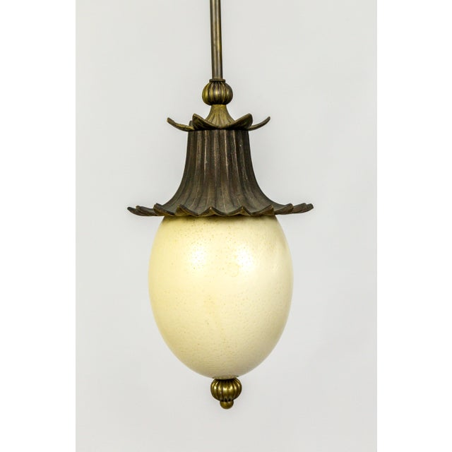 A lovely, hand crafted pendant light made with an ostrich egg and antique metal decorative elements on a long, brass stem....