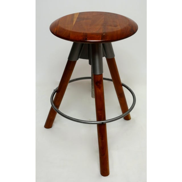 Modern/Contemporary gum wood & metal height adjustable swivel stool with three legs that are metal rimmed and a round seat.