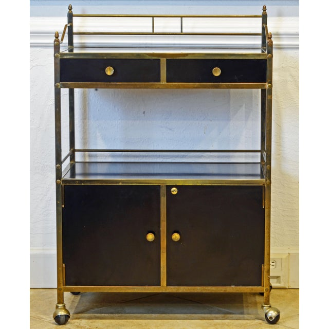 This well designed bar cart or server dating to the 1960-1970 features frames of solid brass and surfaces of black lacquer...
