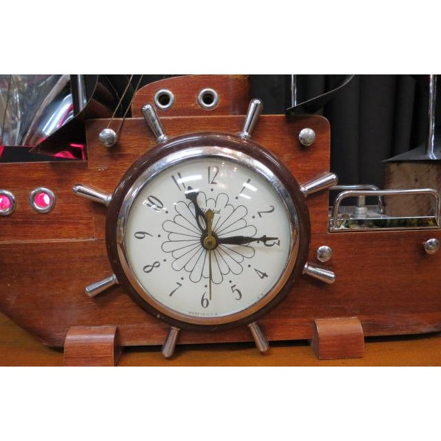 Mahogany ship hull with an electric clock in the center surrounded by a ship wheel. 3 chrome sails with chrome flags....