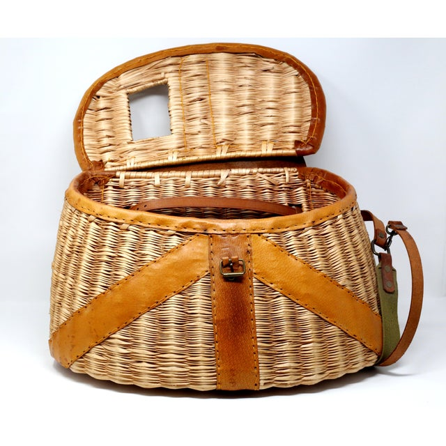 A vintage wicker and leather basket for fly fishing. High quality and in excellent condition. Includes carved wood fish...