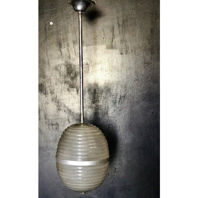 This is a beautiful, Italian Murano pendant light with a thick, milk glass bulb, circa 1960.