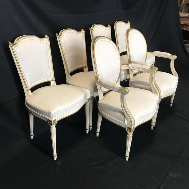 Elegant highly decorative set of 6 antique French Louis XVI dining chairs that date to the 19th century. The classic form...