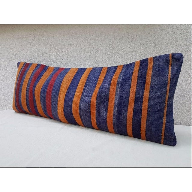 "This beautiful 16"" x 40"" pillow cover was made from an authentic, vintage Turkish kilim rug handwoven in the 1970s. Bright..."