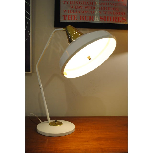 Iconic desk lamp by Bill Scarlett for Swivelier. Hood moves up and down and side to side on ball joint. When lit, light...