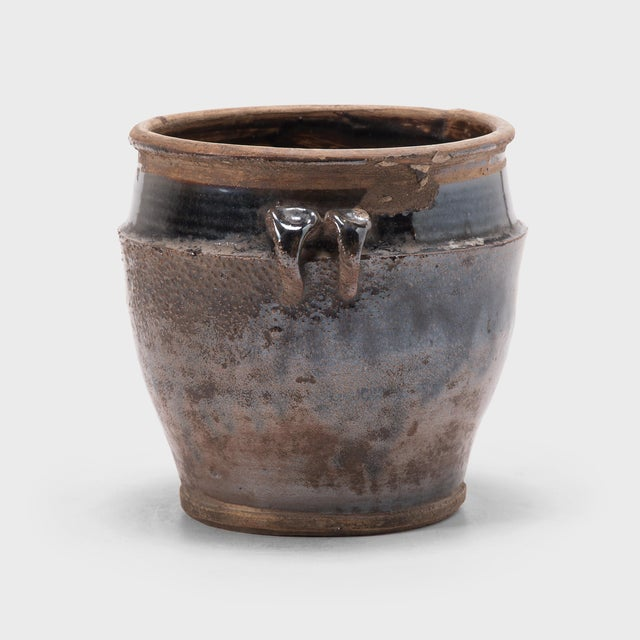 A thin, dark glaze clings to the angular shoulders of this petite jar, dripping down the textured sides in rivulets of...