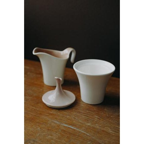 Adorable ceramic cream and sugar set. Glossy taupe and white glazing.