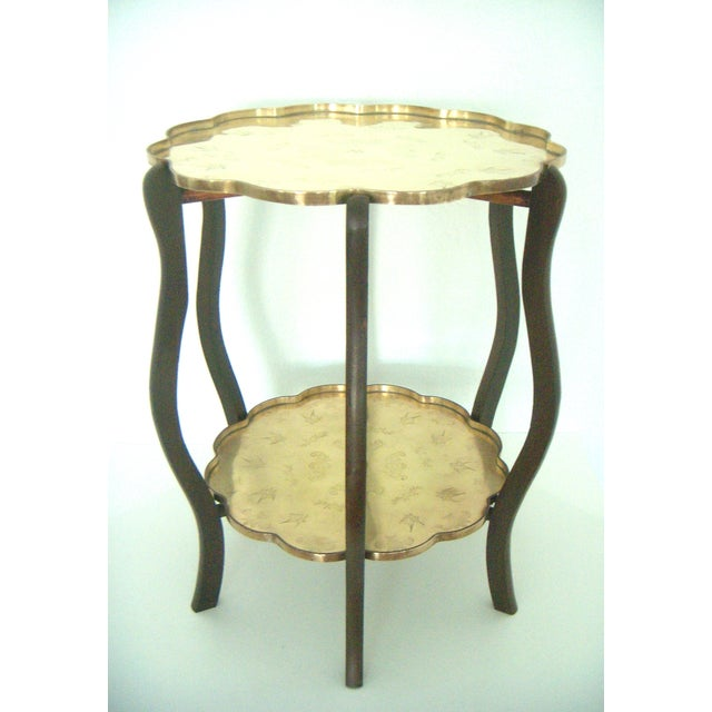 Quite an unusual older/vintage folding table with two hand chased scalloped edged solid brass trays. The brass trays...