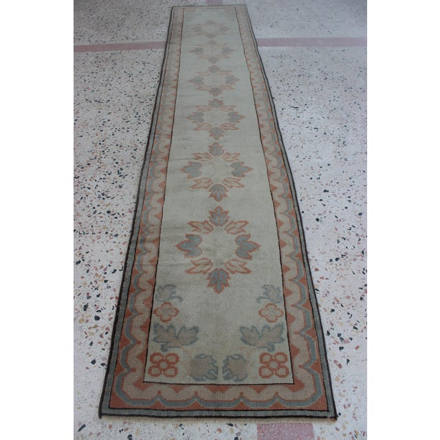 This vintage oushak rug is hand woven and features geometric design in cheerful colors, beige and light green. The rug is...