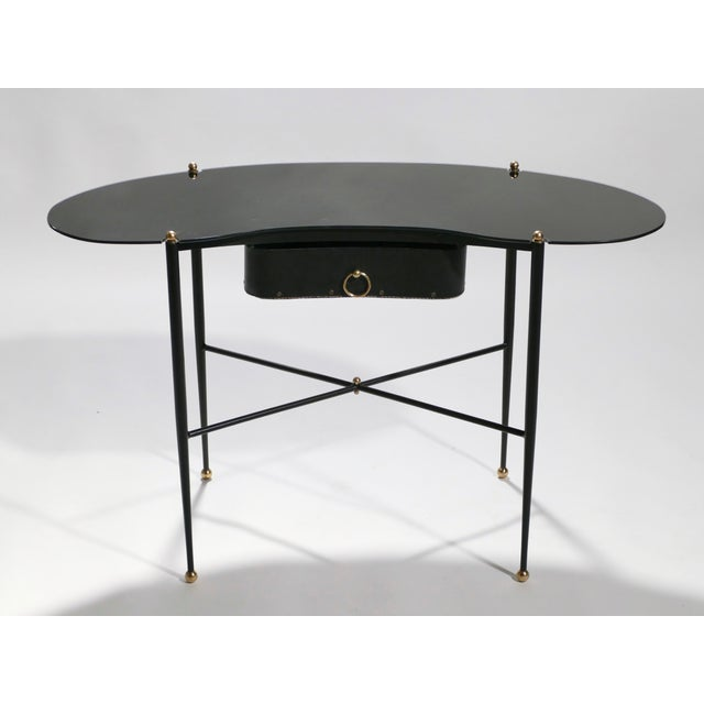 This vanity desk and stool set are rendered in monochromatic black, created by black metal, black opaline, and black piqué...