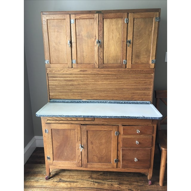 This is an early 20th century kitchen piece. It has an enamel top in good condition. The tambor door and two drawer...