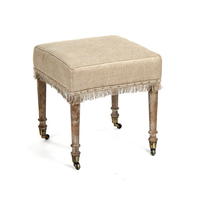 Stool upholstered in hemp linen with nail heads over fringe trim on limed grey oak legs with casters.