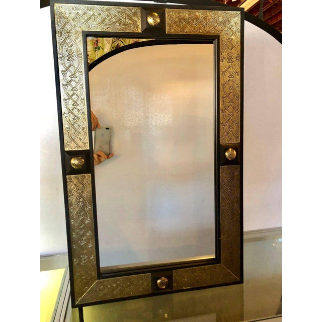 Pair Of Hollywood Regency Style Gold Brass Morrocan Mirrors. Each having a rectangular frame of ebonized wood flanking a...