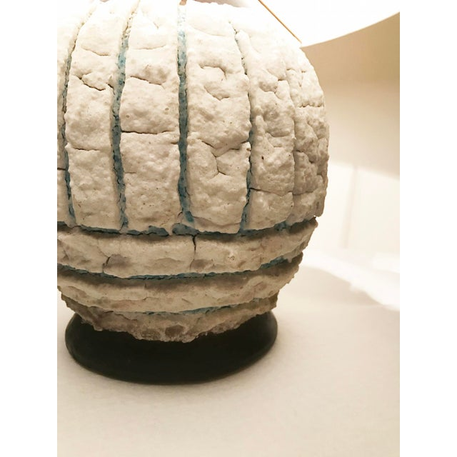 French mid-century pottery table lamp featuring a hand thrown ball shaped base in divided sections of white textured...