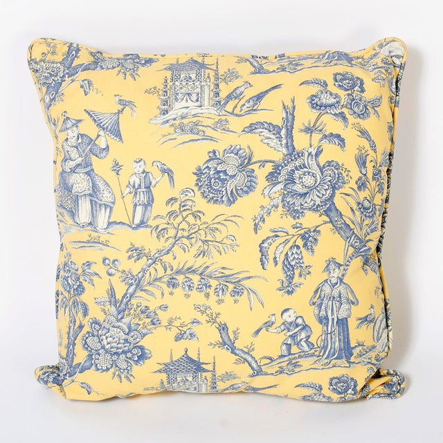 Classical chinoiserie French toile style linen pillows with blue figures and flowers over a yellow background. Discreet...