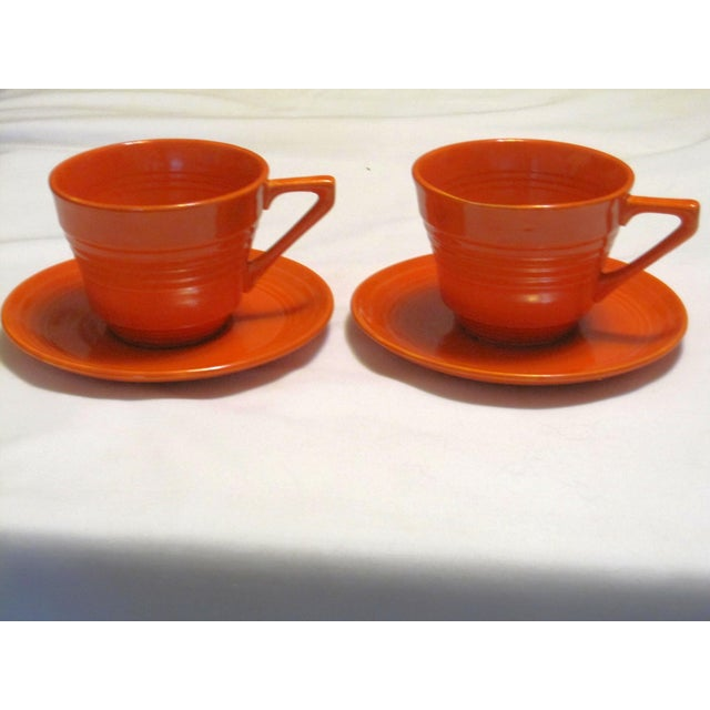 "A pair of Mid-Century Harlequin red cups and saucers in very good condition. The cups have a top diameter of 3 5/8"" and a..."