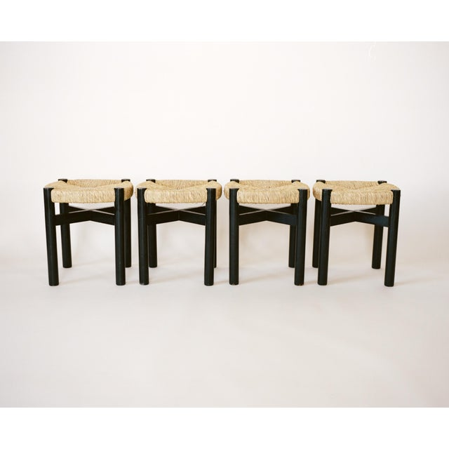 A set of 4 black oak wood stools with woven rush seats by Charlotte Perriand circa 1948. Perriand produced these stools...