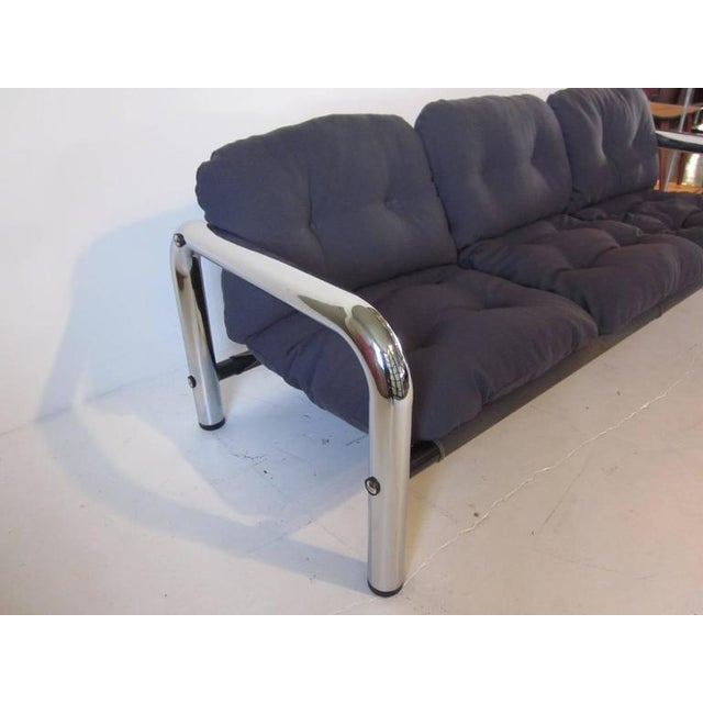 A modern styled tubular chrome metal sofa with charcoal toned canvas sling support topped with comfy gray steel blue...