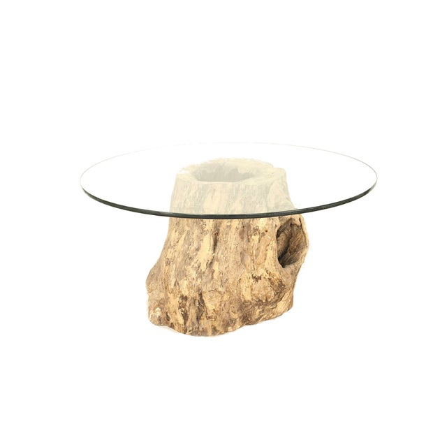 Rustic Adirondack style large tree trunk base dining table supporting a round glass top.