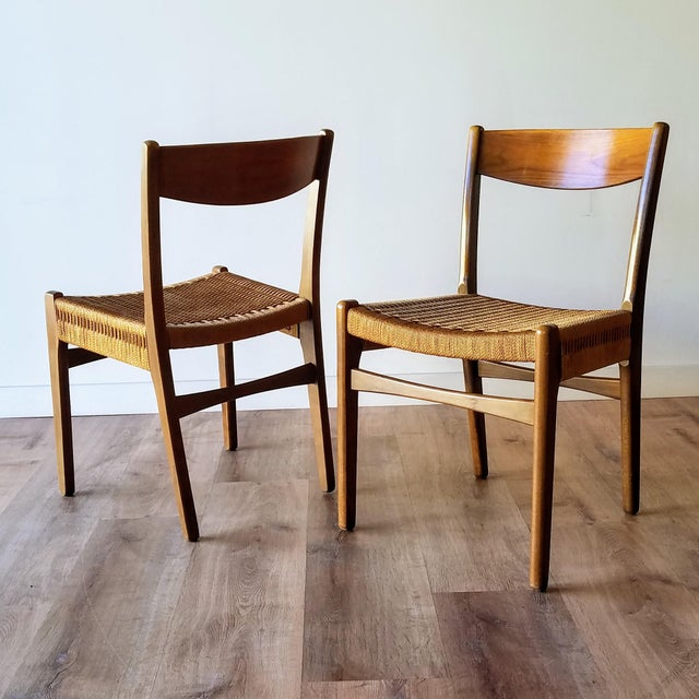 A pair of Swedish Mid-Century Modern rope dining chairs. These chairs feature a two-component stretcher that is connected...