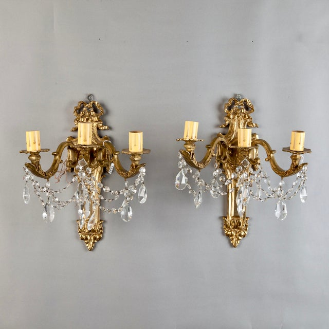 Gorgeous pair of French wall lamps or sconces. Features include: brass frames with a ribbon crest, acanthus leaf...