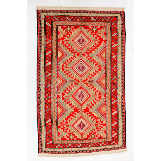 This vintage Afghan kilim rug measures 5.3'W x 8.3'L. Shades of red and cream with black details are woven to create a...