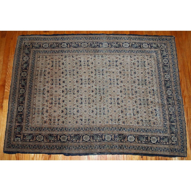 Antique Persian tabriz hajalili rug in beige, brown and blue wool. The rug is from the end of 19th century, it has one cut.