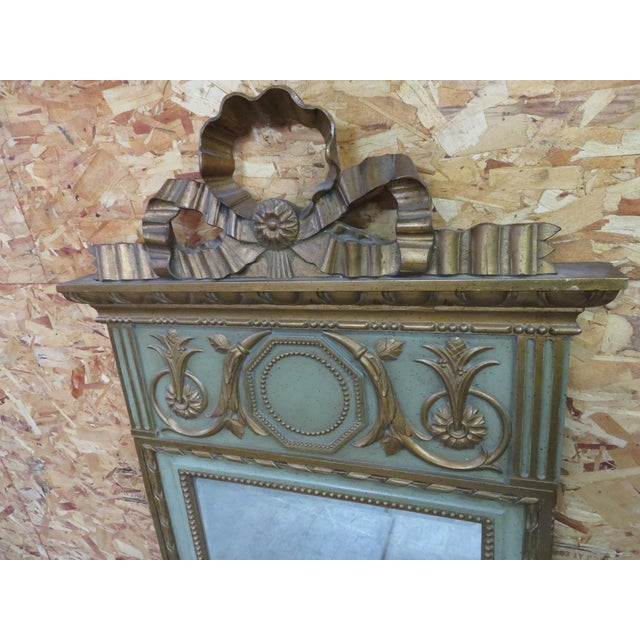Italian Style mirror, carved ribbon crest and other carved designs throughout highlighted in gold paint.