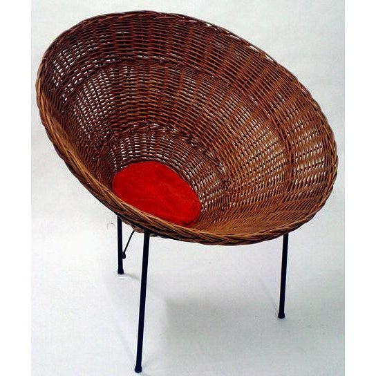 A conical form woven wicker basket lounge chair with a single button pillow cushion raised on a three leg wrought iron...