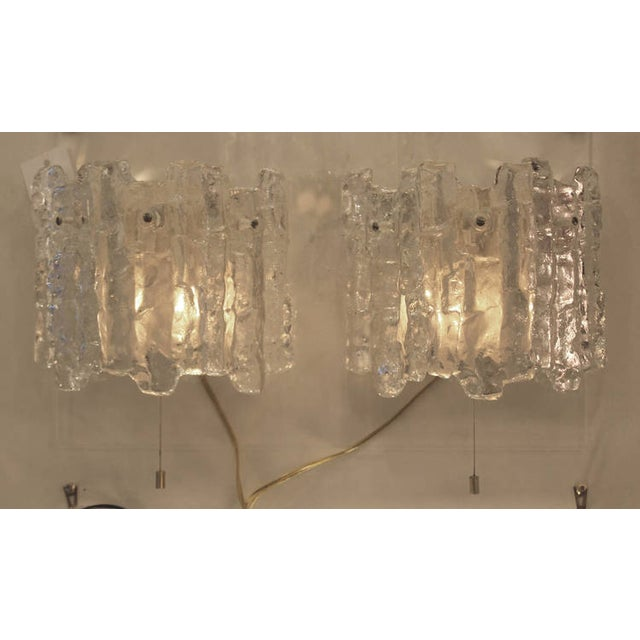 Each sconce features three icicle textured glasses and two sockets with a pull switch