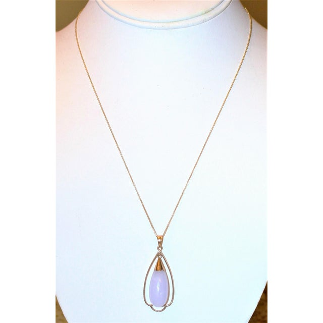 Large pale lavender jade drop pendant framed in a 14k gold with gold findings and hanging from a fine 14k gold chain. The...