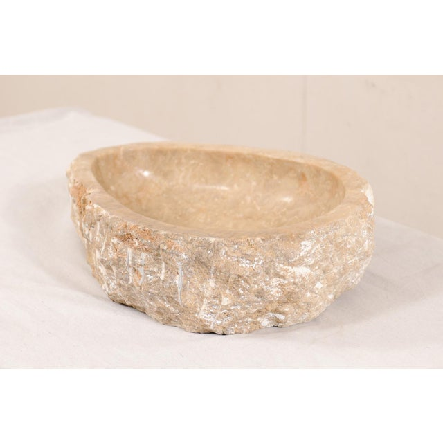 A single natural onyx sink basin with original live edge. This carved vessel sink, created from a rough onyx rock, has a...
