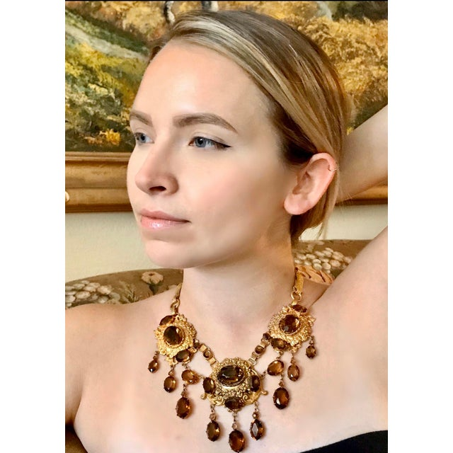 Large, ornately designed gold tone bib necklace prong set with smoky topaz faceted glass oval stones. This large statement...
