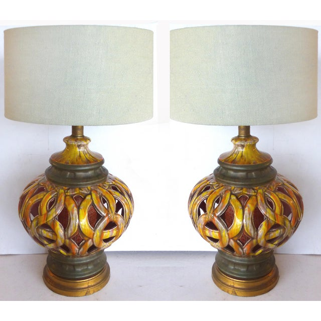An over-scale pair of pierced and drip-glazed ceramic table lamps with interior lights. The interior shade is acrylic and...