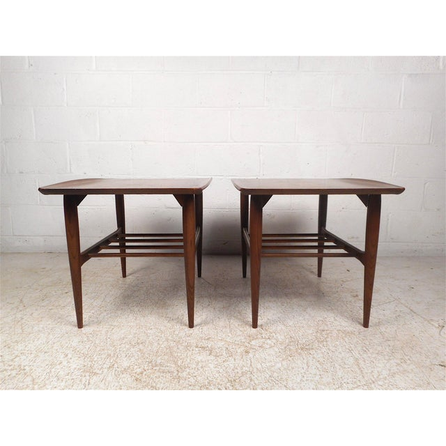 Stylish pair of midcentury end tables by Bassett Furniture Company, circa 1960s. Sturdy walnut construction. Raised edges...