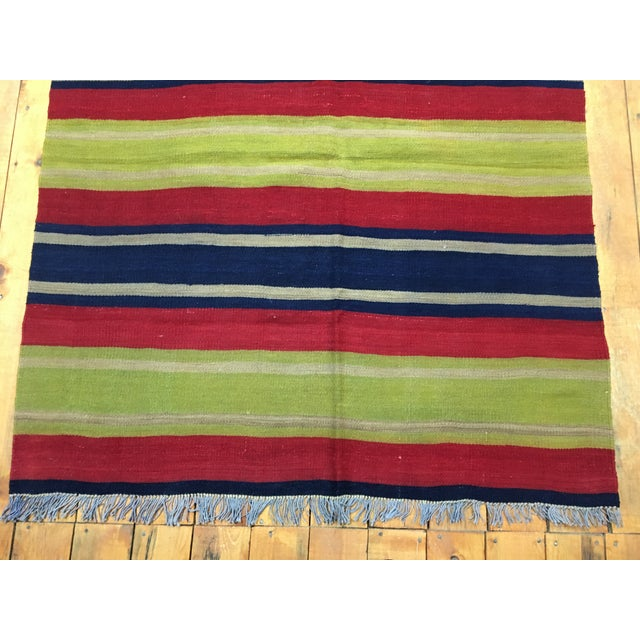 This is a striped Turkish Cecim kilim rug. The piece was made in the 1980s.