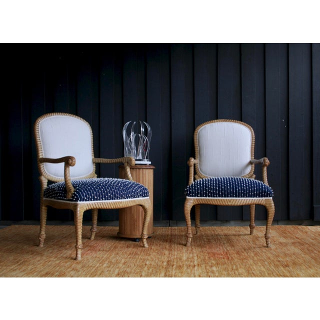 Newly upholstered in textural fabrics and braided unbleached cotton trim, this pair of carved rope and tassel armchairs...