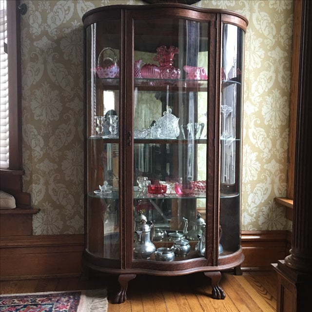 Beautiful antique tiger oak curio cabinet with 3 curved glass sides, unusual mirrored back and 3 glass shelves, claw feet....