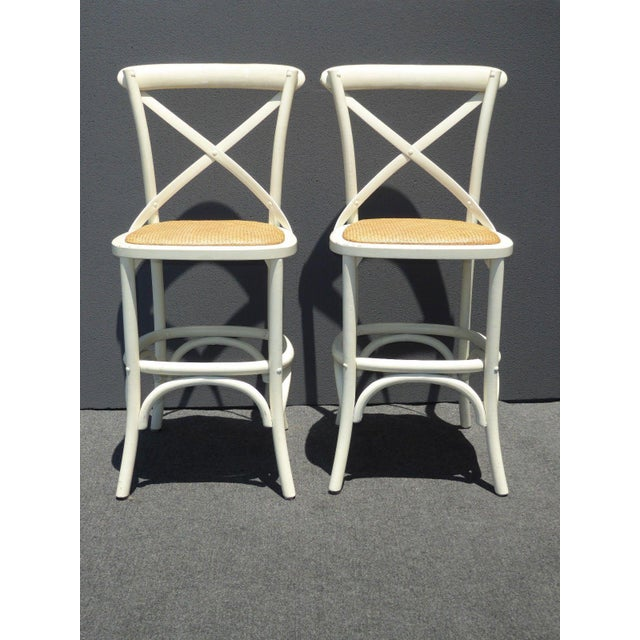 A pair of vintage French Country style white rye seats bar stools. In good vintage condition, with wear that is usual for...