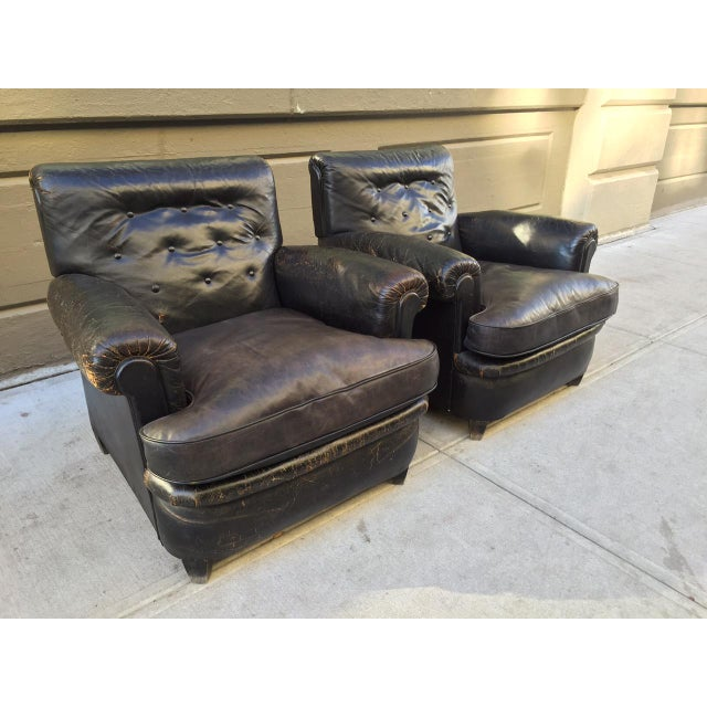Pair of 1930s English distressed leather club / lounge chairs. Has wood bracket feet and tufted back.
