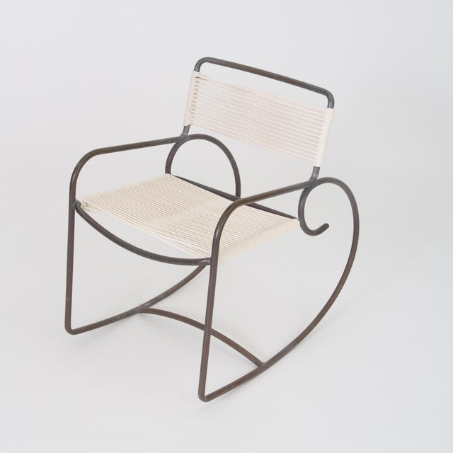A single bronze rocking chair designed by Walter Lamb and produced by Brown Jordan. The chair has a sculptural shape, with...