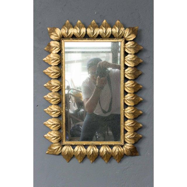 Rectangular framed mirror bordered with gilt leaves, Spanish, 1950s.