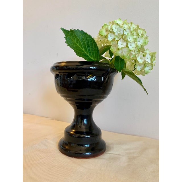 This hand-thrown terra cotta vase is glazed in black with a subtle perforated pattern along the lip. It has a striking...