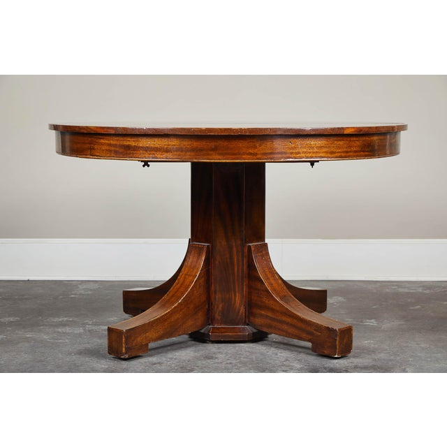 A 19th century English Mahogany Pedestal Table. Features two leaves and an inlaid banding on top and legs. Simple, clean...